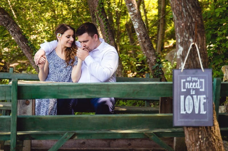 Engaged man and woman sitting on park bench